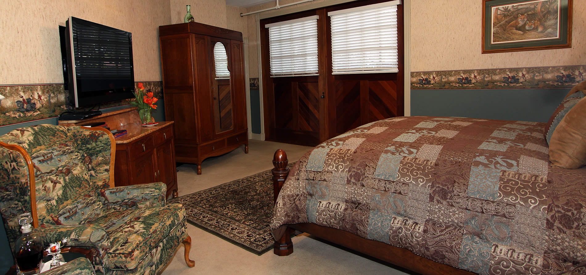 fox's den guest room bed, tv and large wooden doors