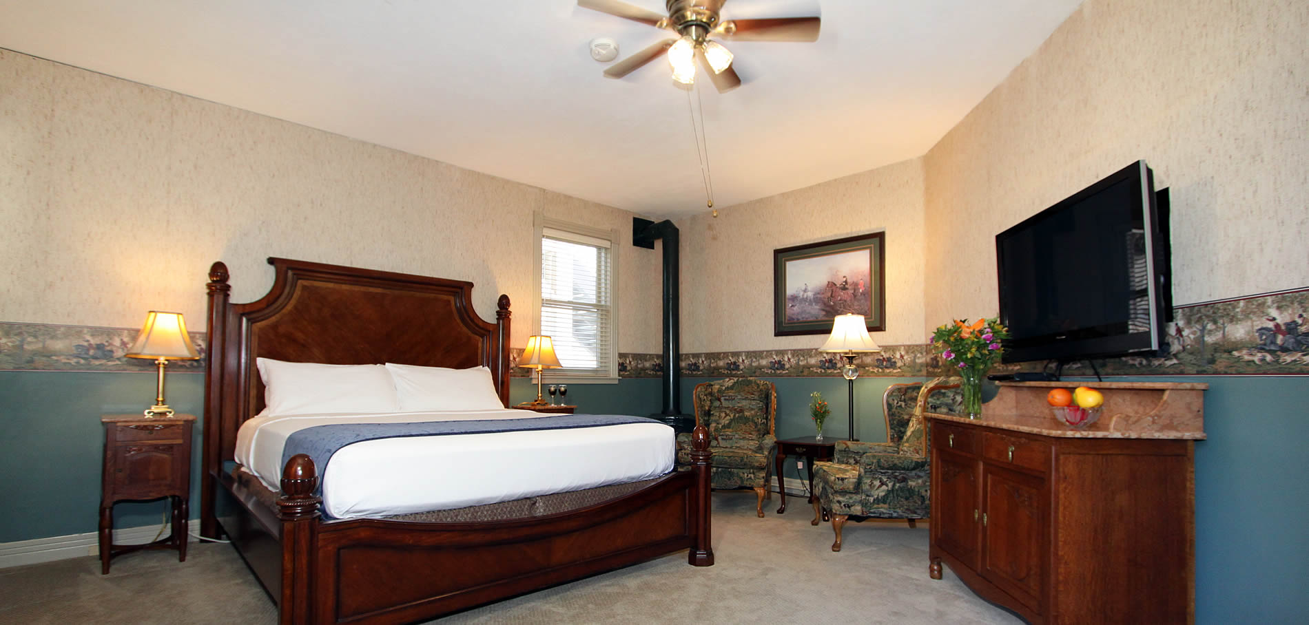 pheasant dreams room with bed, chairs and firestove